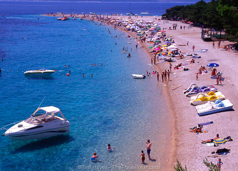 Families on holiday soak up sun and swim in the Dalmatian coast's blue water in the resort town of Bol on the island of Brac (Brach).