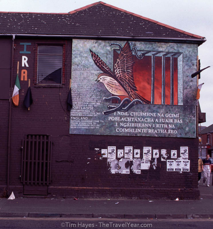 Cartoon mural in Catholic Falls Road area of Belfast depicting a caged bird escaping from behind bars.XXXXInscription reads (In Irish), ''IRA / I NDIL CHUIMHNE NA GCIMI POBLACHTANACHA A FUAIR BAS I NGEIBHEANN I RITH NA COIMHLINTE REATHA SEO.''