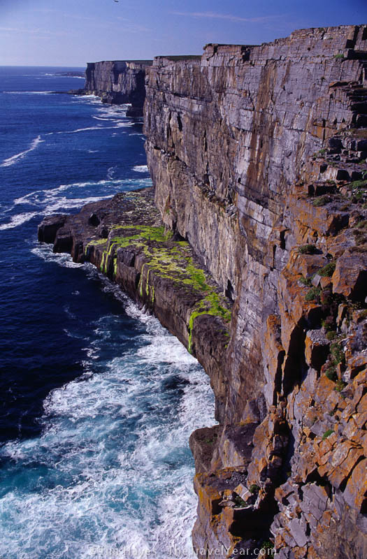 Surf crashes along the cliff-covered coast of Inishmore Island, County Galway. The 87 meter-high view looks out from the 3,000-year-old Dun Aengus ring fort, inhabited from 1100 BC to 1000 AD.
