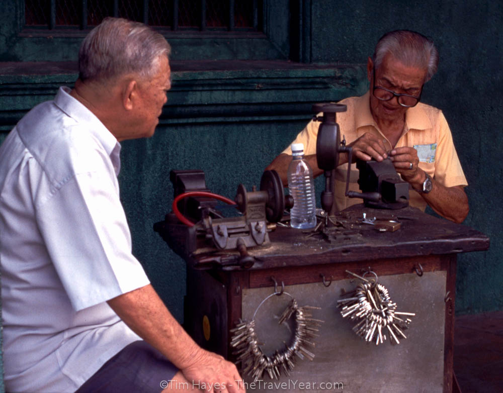Two old men work outside in Penang, Malaysia, making keys.